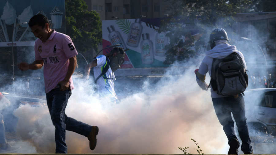 Venezuelans run away from tear gas during scuffles with security forc