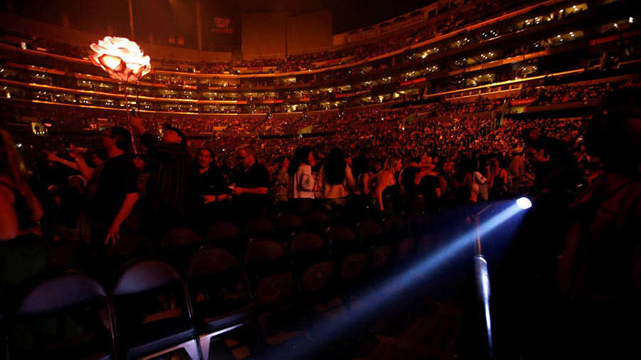 An usher uses a flashlight to clear the front row during an earthquake ahead of a concert by Shawn Mendes at Staples Center in Los Angeles