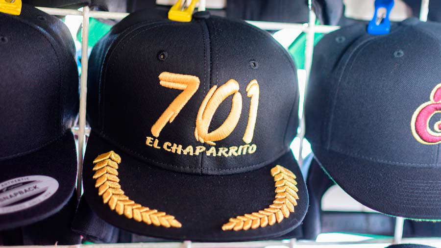 View of caps displayed for sale with embroideries of the number 701 -