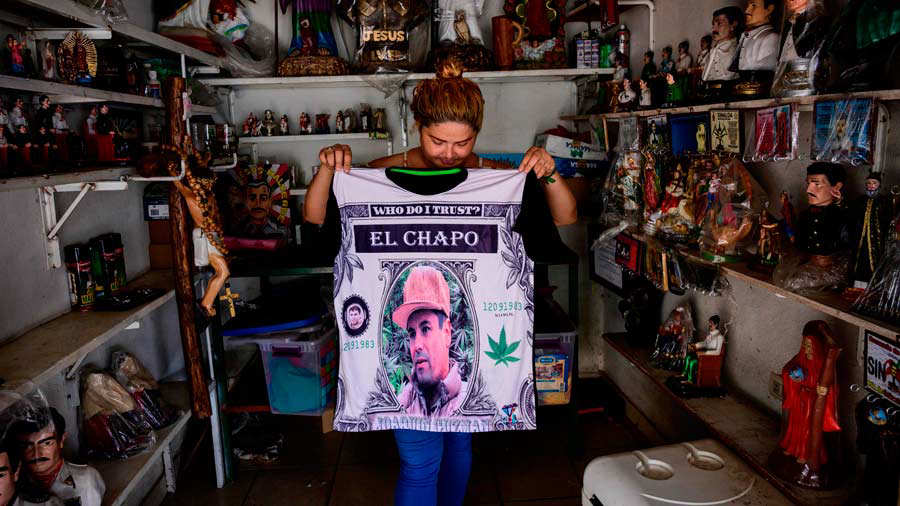 A vendor shows a shirt depicting a portrait of Mexican drug lord Joaq