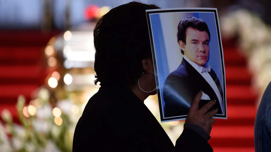 A person holds a picture of late Mexican singing legend Jose Jose dur