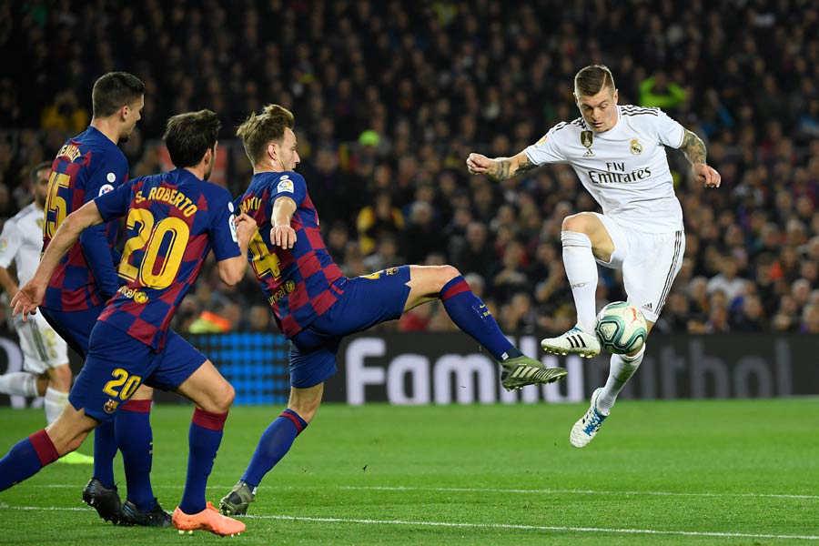 Barcelona's Croatian midfielder Ivan Rakitic (C) challenges Real Madr