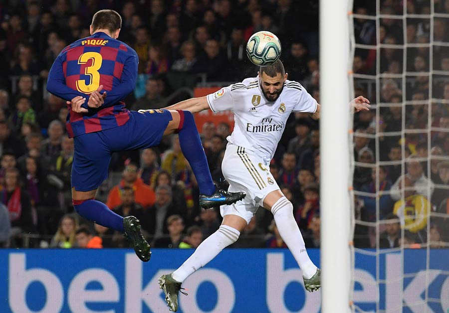 Barcelona's Spanish defender Gerard Pique (L) vies woith Real Madrid'