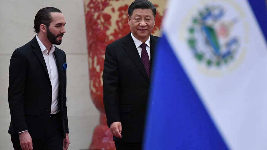China's President Xi Jinping (R) walks with El Salvador's President N
