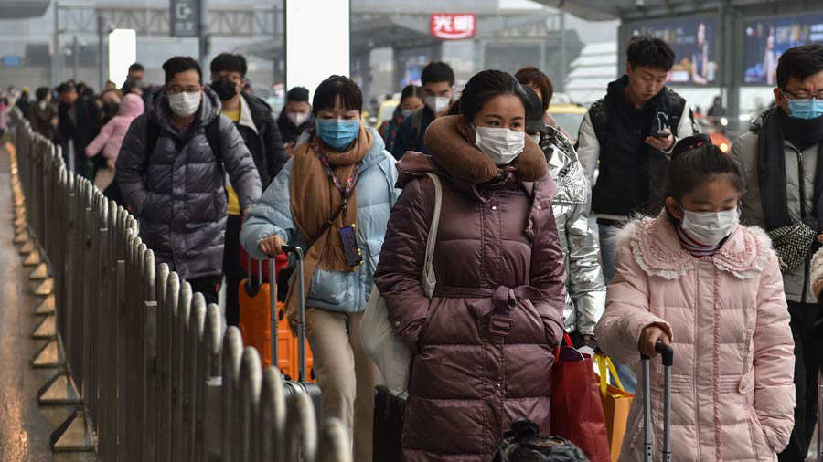 People wearing masks arrive at Hongqioa train station as they head ho