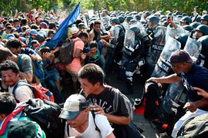 Members of the Mexican National Guard scuffle with Central American m