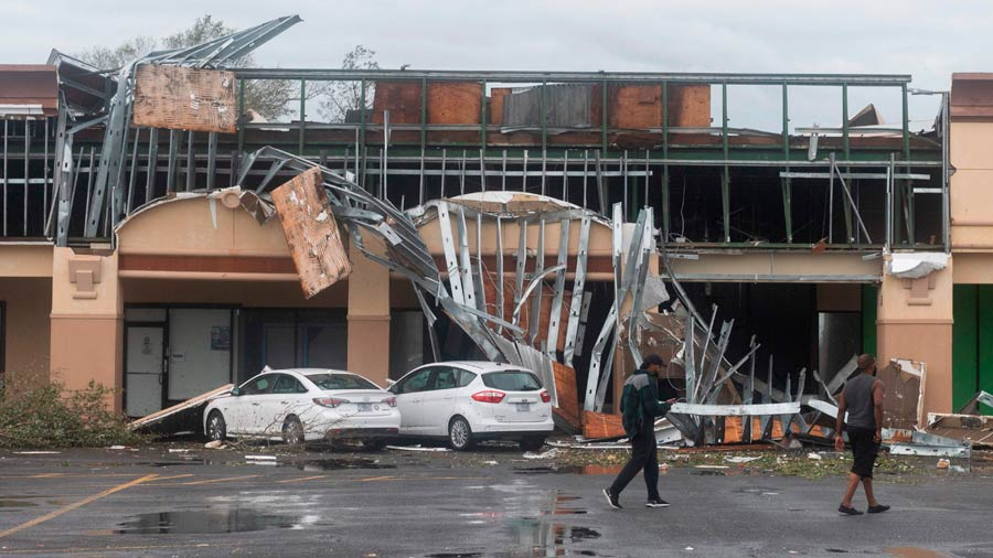 People walk past a destroyed building after the passing of Hurricane