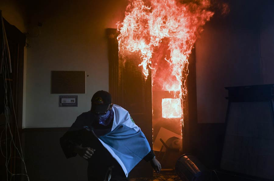 A demonstrator runs after setting on fire an office of the Congress b