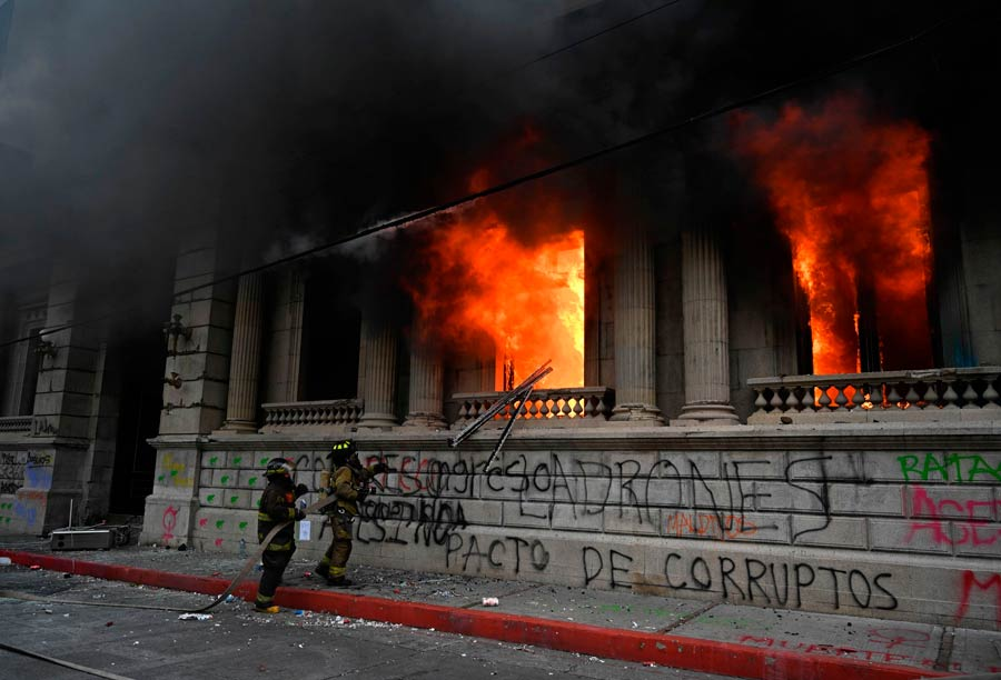 Firefigthers try to extinguish a fire at the Congress building during