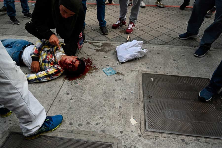 An injured demonstrator lies on the street during a protest demanding