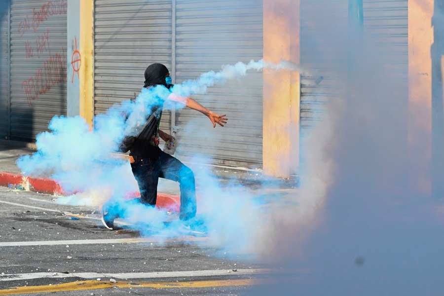 A demonstrator clashes with riot police during a protest demanding th